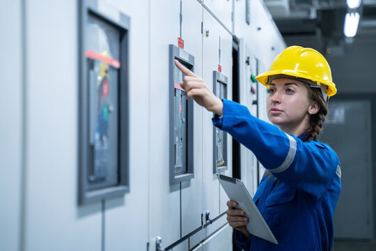 Woman Electrical Engineer working front HVAC control panels, Technician daily check solar cell controls system for security functions in service room at factory.Energy,Ventilation,Air Conditioning.