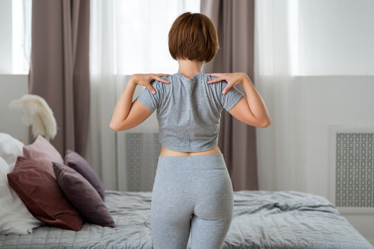 Young woman doing morning exercises in the bedroom