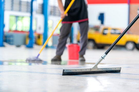 Select the focus mop, service staff man using a mop to remove water in the uniform cleaning the protective clothing of the new epoxy floor in an empty warehouse or car service center.