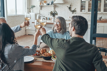 Fototapeta Happy multi-generation family toasting each other and smiling while having dinner together obraz