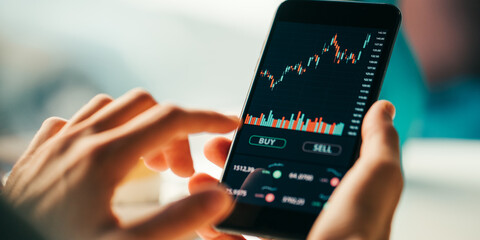 Woman touching mobile phone investing application. Stock market investment app in hand. Screen...