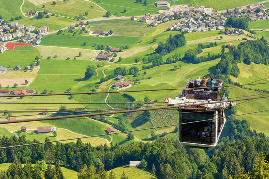Tourists (faces not visible) climbing the cable car in an open car up Mount Stanserhorn in Switzerland and admire the magnificent aerial panorama of central Switzerland, mountains, villages and forest