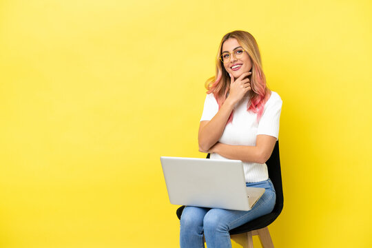 Young woman sitting on a chair with laptop over isolated yellow background happy and smiling