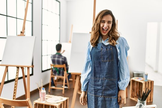 Young artist woman at art studio winking looking at the camera with sexy expression, cheerful and happy face.
