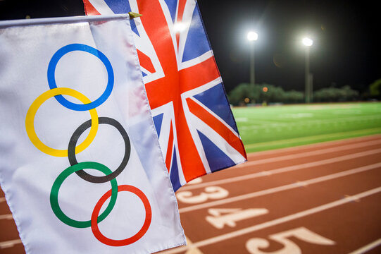 MIAMI, USA - AUGUST 15, 2019: An Olympic and UK Union flag wave together under the floodlights of a red athletics track.