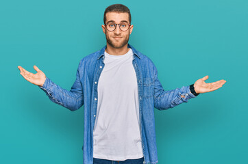 Young caucasian man wearing casual clothes clueless and confused expression with arms and hands...