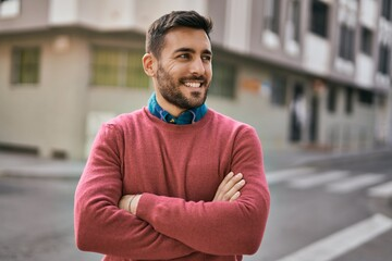 Young hispanic man with arms crossed smiling happy standing at the city.