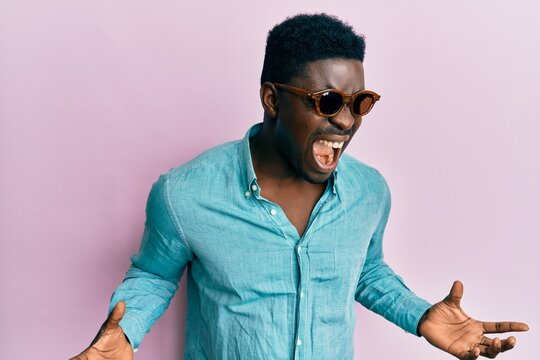 Handsome business black man wearing stylish sunglasses crazy and mad shouting and yelling with aggressive expression and arms raised. frustration concept.