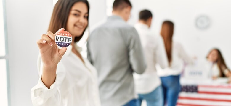 Group of young american voter people putting vote in ballot. Woman smiling happy and holding i voted badge at electoral center.