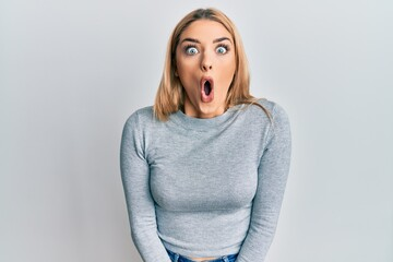 Fototapeta Young caucasian woman wearing casual clothes afraid and shocked with surprise expression, fear and excited face. obraz