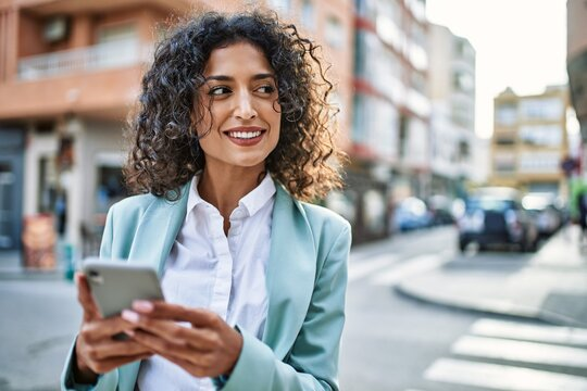 Young hispanic business woman wearing professional look smiling confident at the city using smartphone