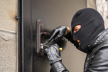 Fototapeta man in a black balaclava mask opens a locked door with a lock pick. The robber breaks into the house. Robbery of a private house. Criminal concept obraz