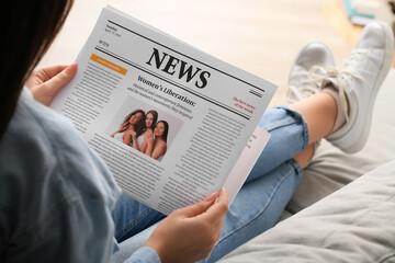 Obraz Young woman reading newspaper at home, closeup - fototapety do salonu