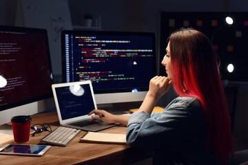 Fototapeta Female programmer working with laptop in office at night obraz