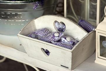 Fototapeta Biała drewniana skrzyneczka z serduszkiem wypełniona fioletowymi ozdobami obraz