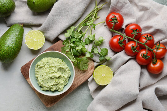 Bowl with tasty guacamole, tomato, avocado and lime on light background