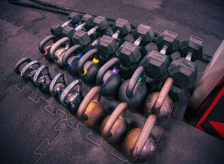 Dumbbells and kettlebells on a gym's floor. A workout template perspective view, photo shot