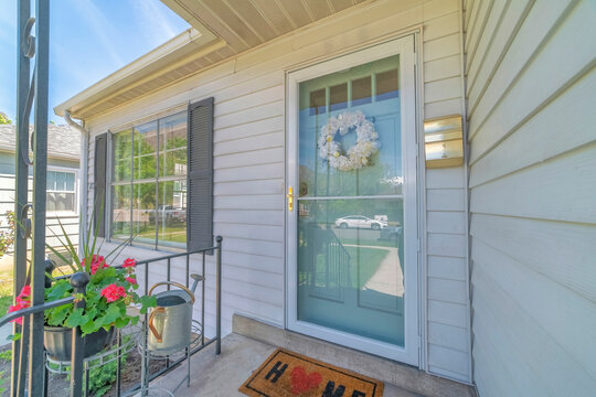 Front view of house on real estate listing with glass storm door and green door