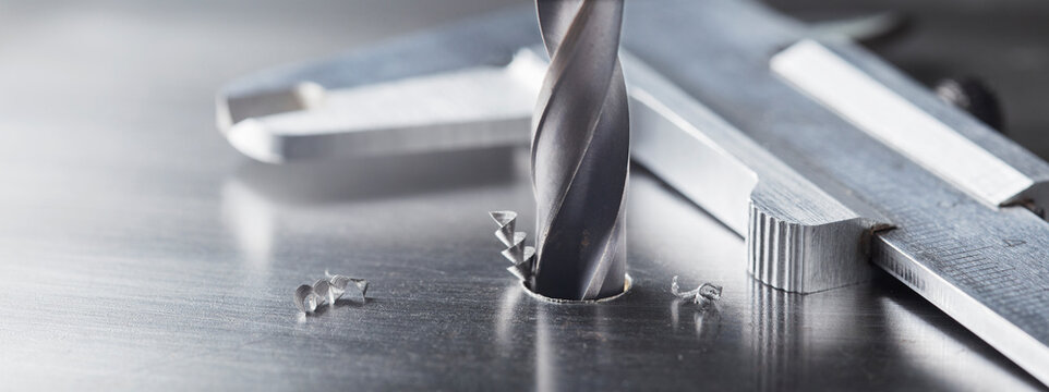 metal drill bit make holes in steel billet on industrial drilling machine. Metal work industry. multi cutting tool and end mill.