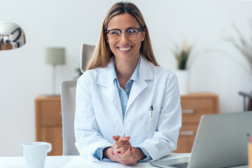 Obraz Mature attractive female doctor looking at camera while working sitting in the consultation. - fototapety do salonu