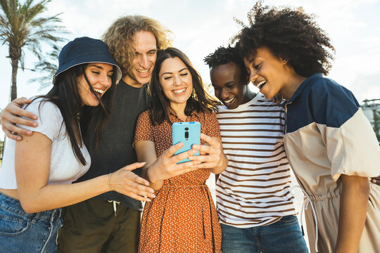 Multiracial group of young people looking at smartphone while walking in the street. Happy hispanic woman showing something to his mixed race friends in her mobile phone while having fun outdoors -