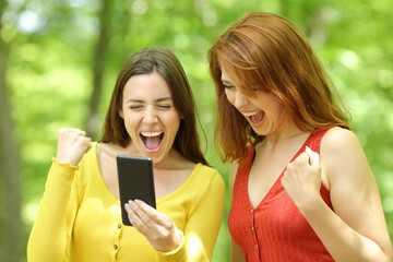 Obraz Two excited women checking smart phone in a park - fototapety do salonu