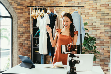 Fototapeta Young and beautiful Asian woman blogger showing clothes in front of smartphone camera while recording vlog video and live streaming at her shop obraz