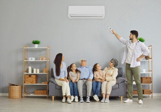 Happy family relaxing on sofa under air conditioning. Man holding a remote control air conditioner makes a comfortable temperature for the family. Concept of the climate system in a modern house.