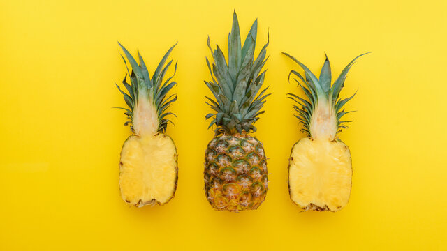 Pineapple fruit on yellow summer background. A whole tropical pineapple and half fruit in a minimalist style on a summer bright yellow background. Long web banner Flat lay