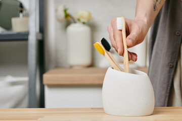 Obraz Hand of female taking one of three wooden toothbrushes in white bowl - fototapety do salonu