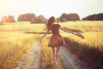 girl dress wheat field / happy summer vacation concept, one model in a sunny field