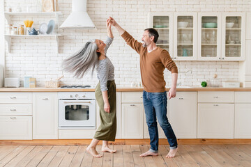 Fototapeta Mature family middle-aged couple wife and husband dancing together in the kitchen, celebrating date anniversary. Active seniors, love and relationship concept. Social distance. obraz