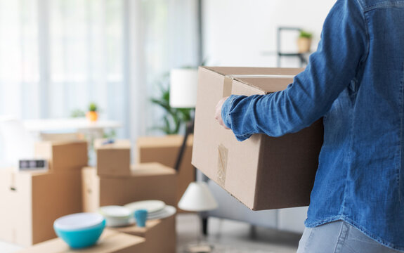 Woman carrying boxes in her new home