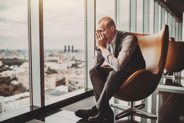 Obraz A stressed outadult caucasian man entrepreneur partly closing face with his hands while sitting on an office armchair next to the window of a modern business skyscraper and looking on the cityscape - fototapety do salonu