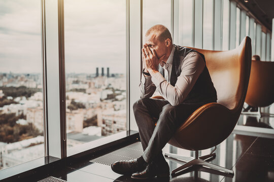 A stressed outadult caucasian man entrepreneur partly closing face with his hands while sitting on an office armchair next to the window of a modern business skyscraper and looking on the cityscape