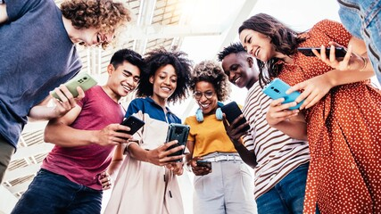 Fototapeta Diverse teenage students using digital smart mobile phones on college campus - Group of friends watching cellphones sharing content on social media platform - Youth, friendship and technology concept obraz