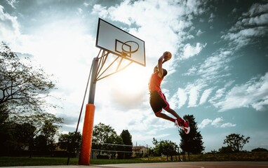 Obraz Street basketball player making a powerful slam dunk on the court - Athletic male training outdoor at sunset - Sport and competition concept  - fototapety do salonu