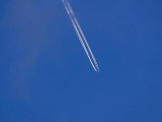 Obraz Smuga kondensacyjna na niebieskim niebie po przelocie samolotu. - fototapety do salonu