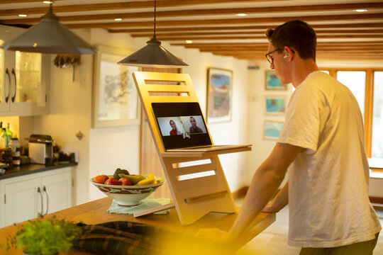 Man video conferencing at laptop stand desk in kitchen