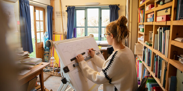 Female architect working at drafting table in home office