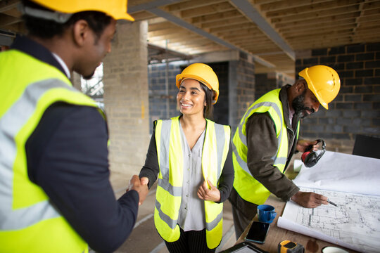 Architect and forewoman shaking hands at construction site