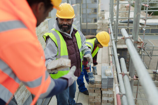 Construction workers laying brick at construction site