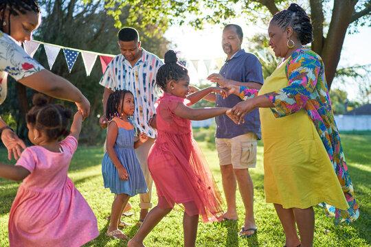 Carefree multigenerational family dancing in summer backyard