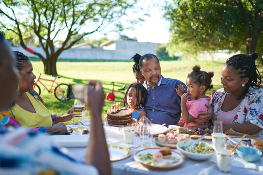 Multigenerational family enjoying birthday lunch in summer backyard