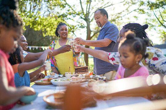 Multigenerational family celebrating birthday at summer patio table