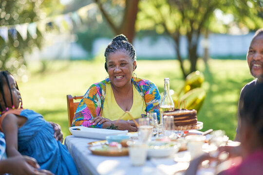 Happy woman celebrating birthday with family at patio table
