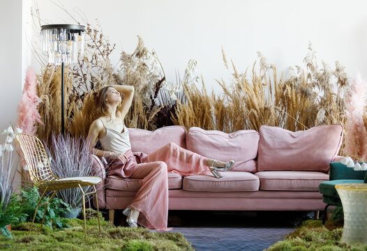 Nice woman posing in a living room in the middle of tall grass