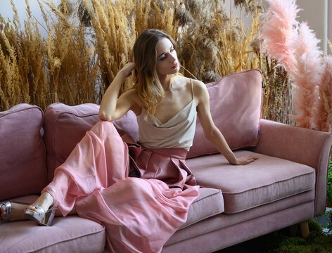 Nice woman sitting on a sofa in a room in tall grass