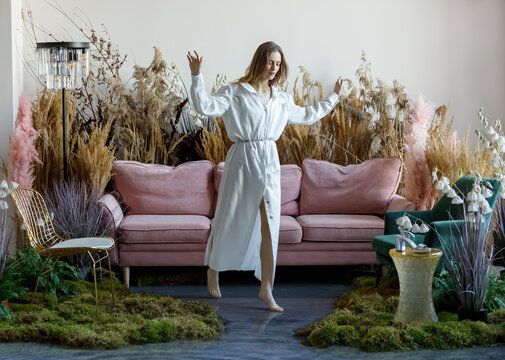 Nice young woman in a room with sofa in the middle of tall grass