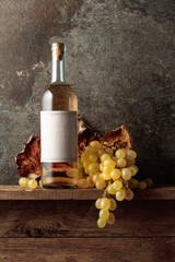 Fototapeta Bottle of white wine with grapes and dried up vine leaves. obraz